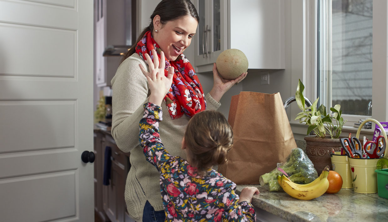 mom and daughter high fiving in kitchen