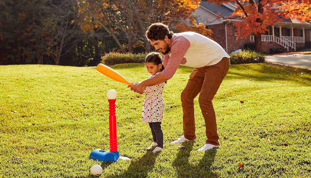 Dad and daughter playing t-ball