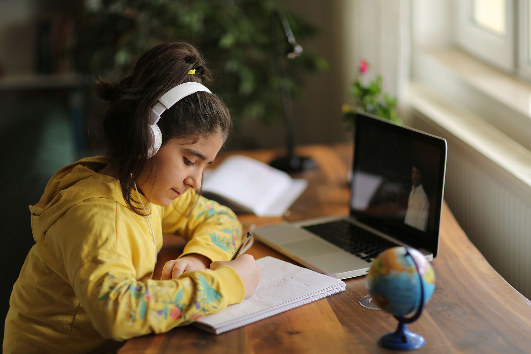 Middle school girl participating in virtual learning at home