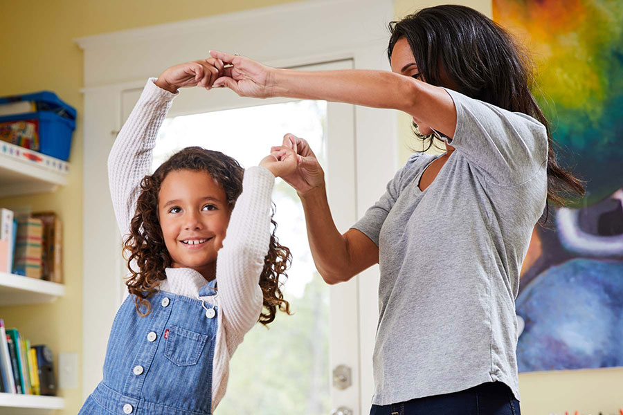 mom and daughter having a dance party in living room