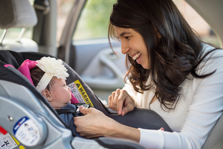 mom buckling infant into rear facing car seat