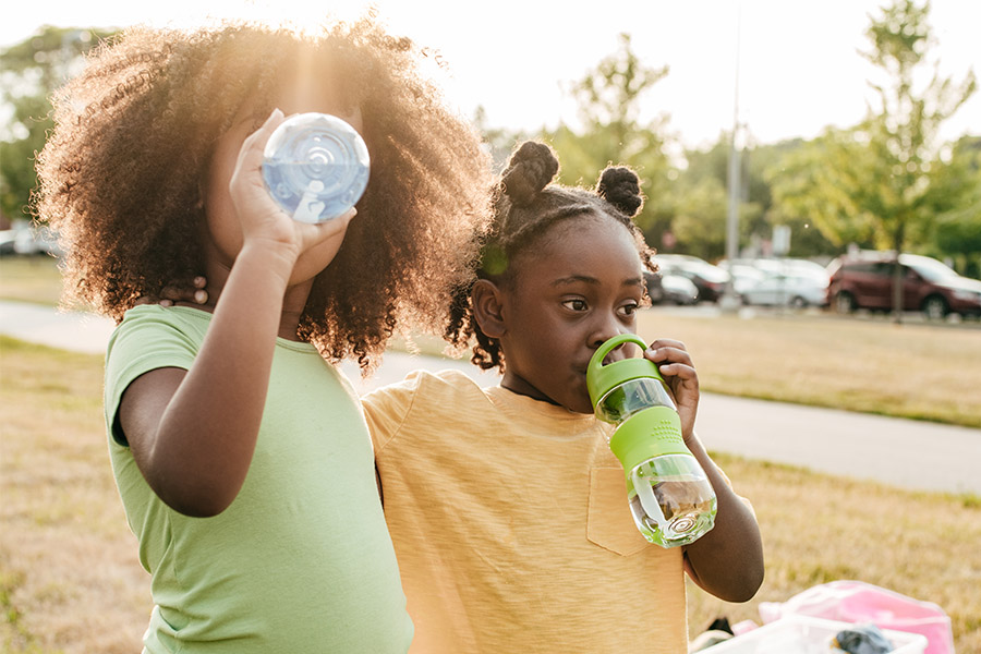 two girls drinking water