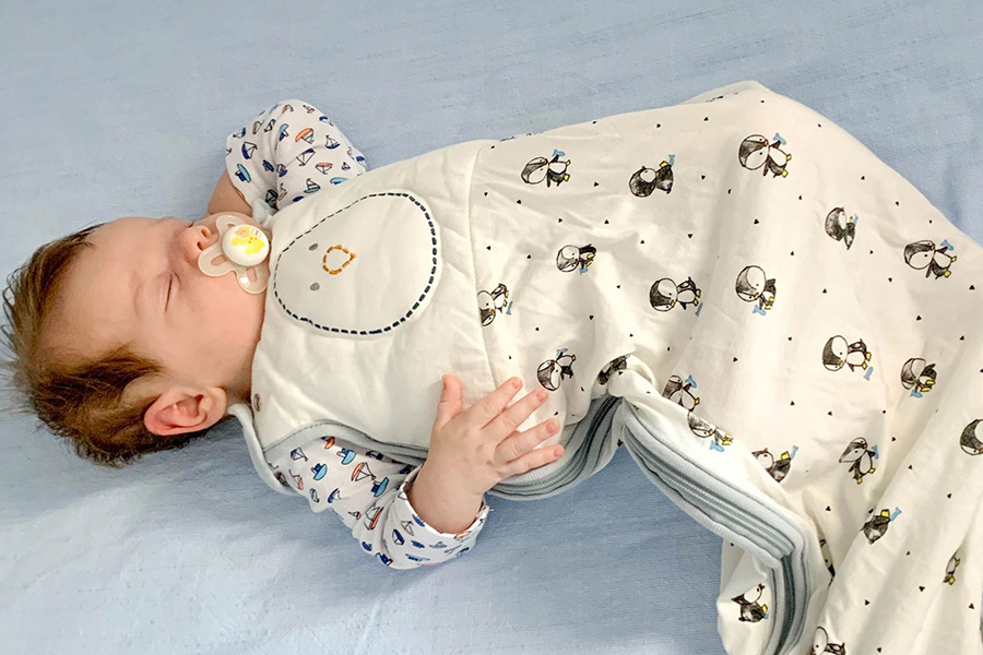 Infant wearing a sleep sack sleeps on his back in a clear crib
