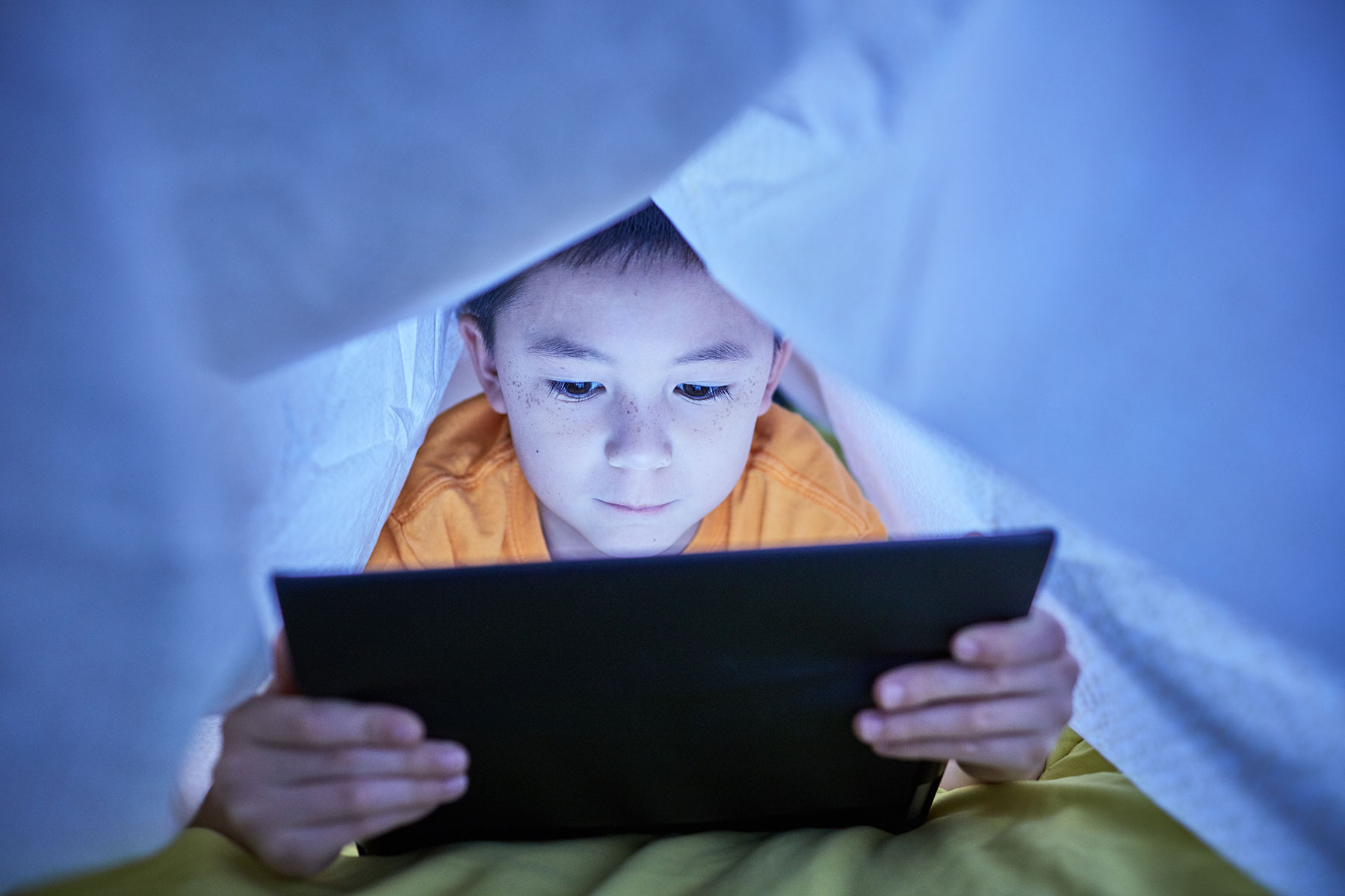 boy on tablet under covers