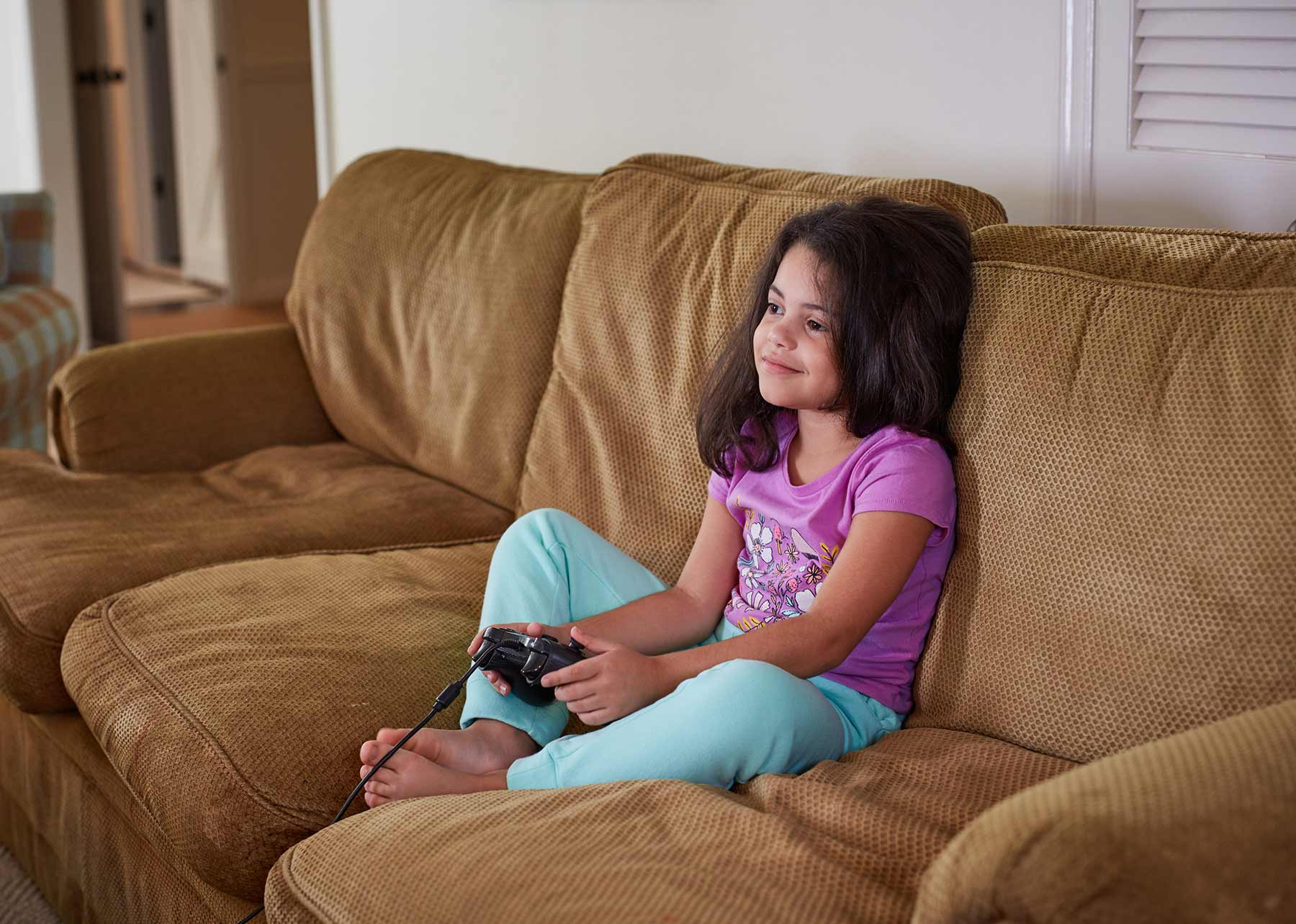 Girl sitting on couch playing video game