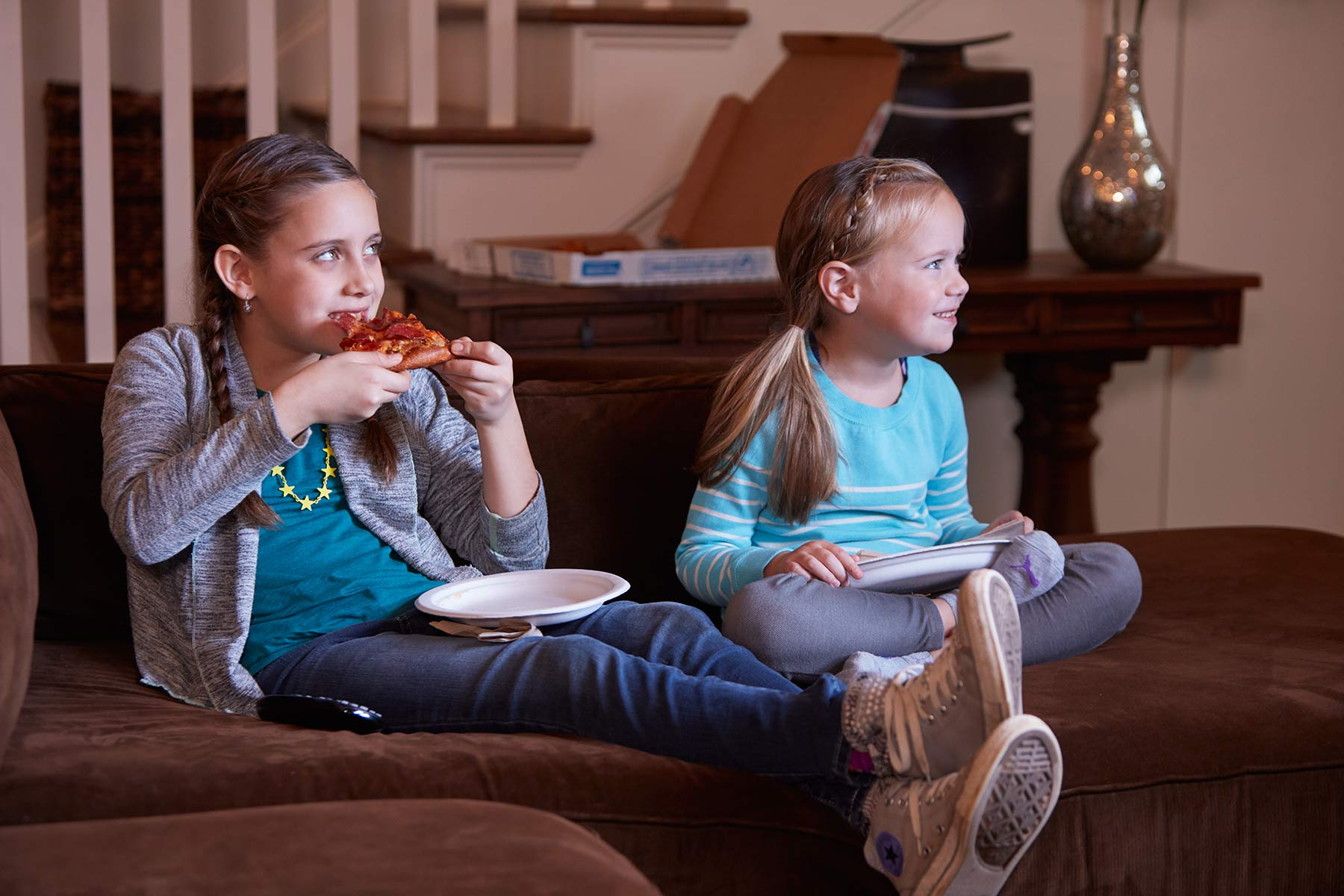 Girls watching TV eating pizza on couch
