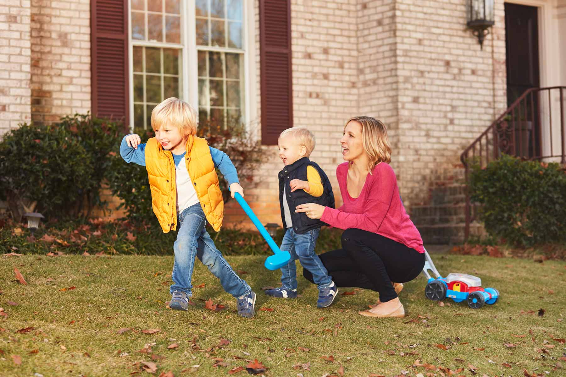 mom playing with sons in front yard