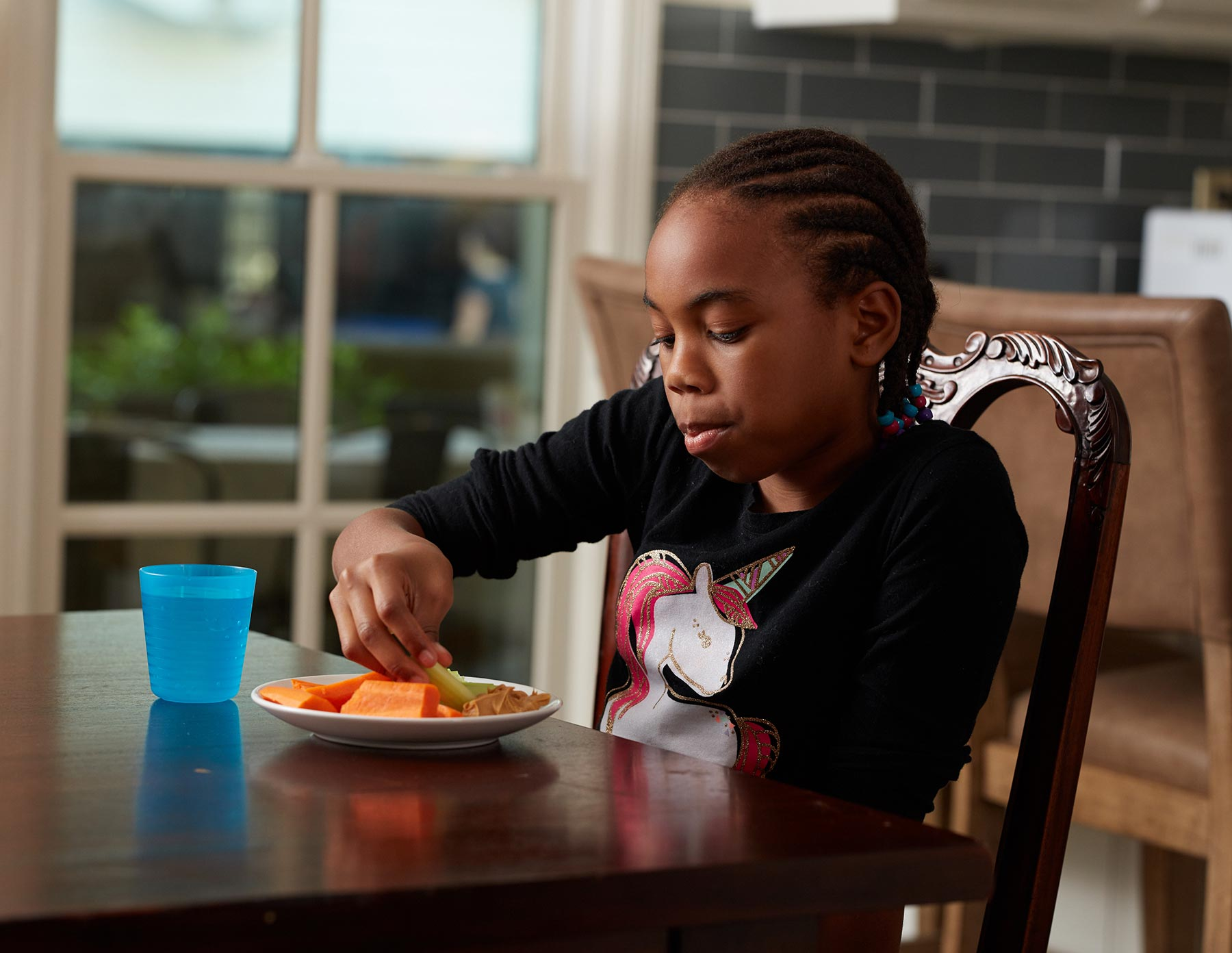 girl eating healthy snacks at table