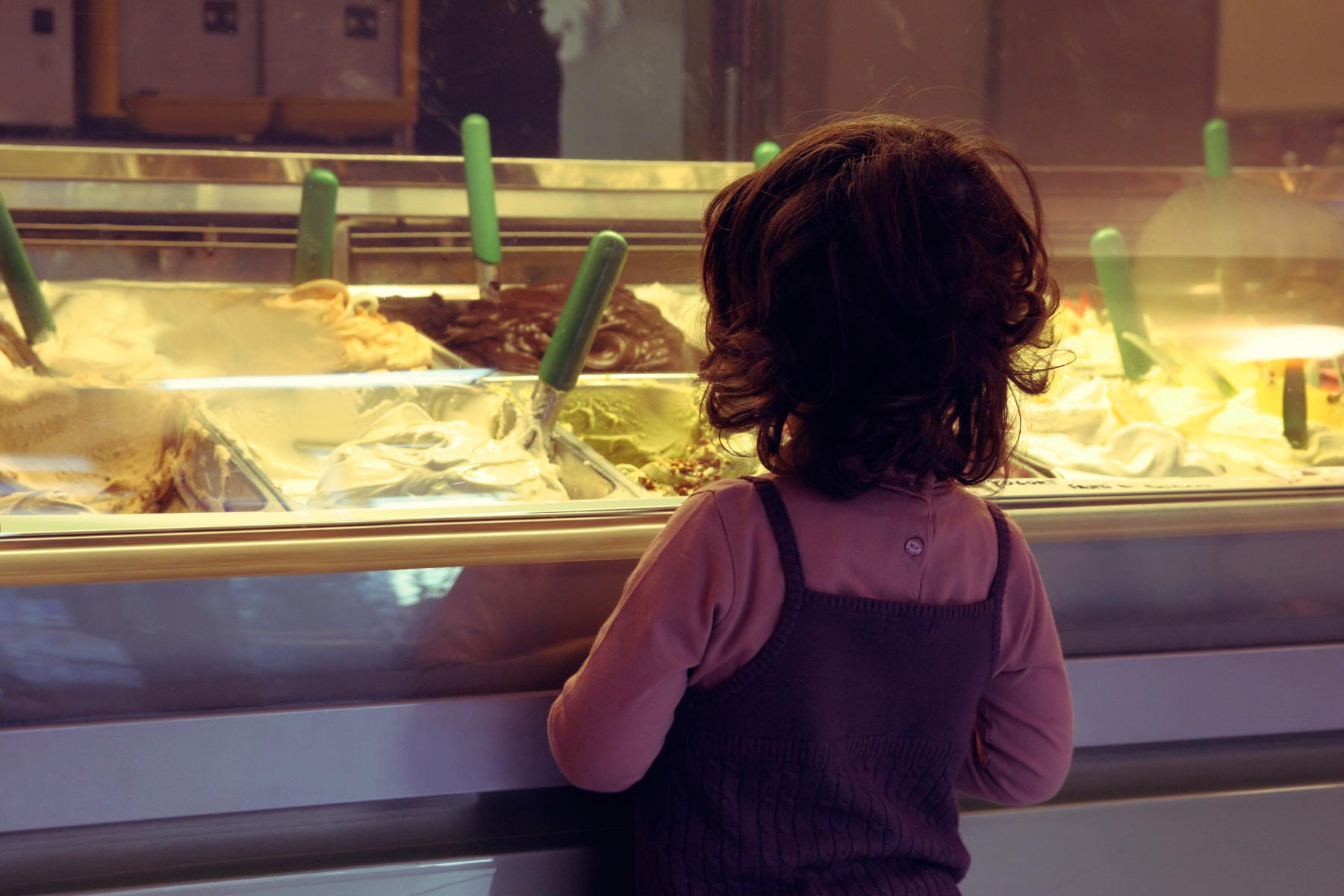 girl looking at ice cream flavors at shop
