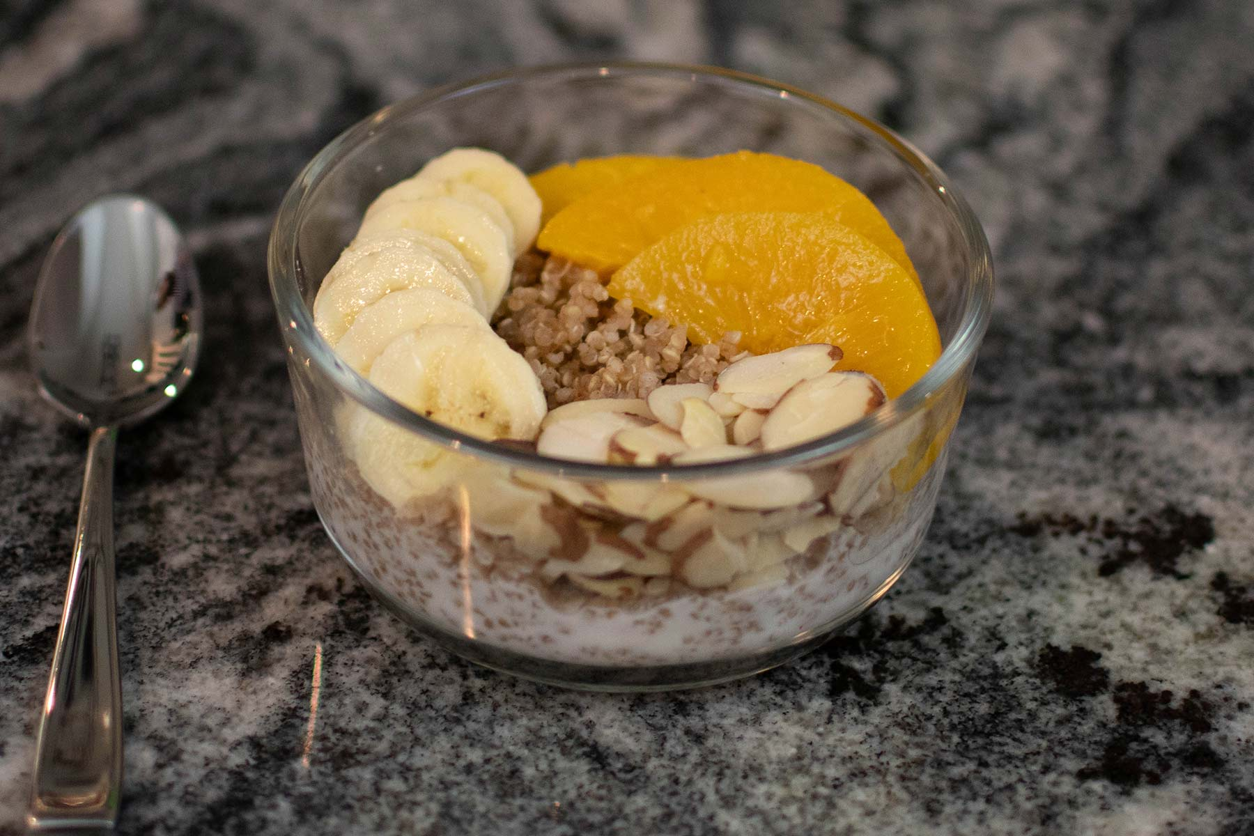 Quinoa breakfast bowl with bananas, almonds, oranges and granola