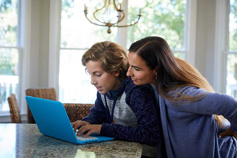 mom and son looking at computer