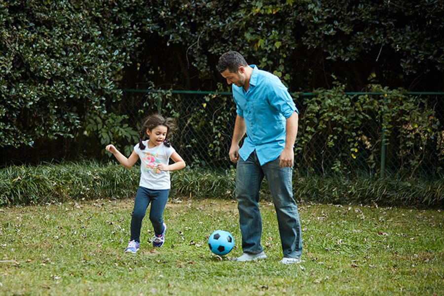 dad and daughter playing soccer