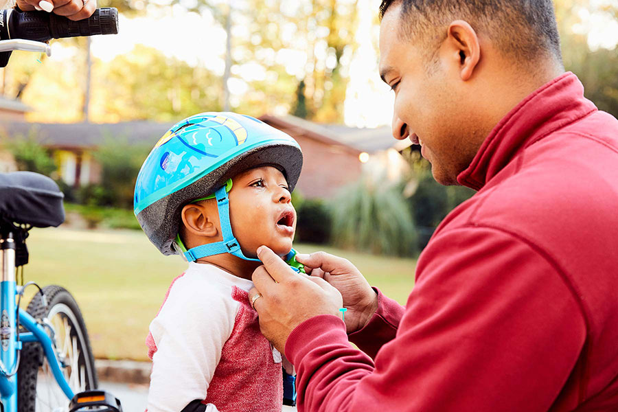 dad consoling son wearing bike helmet