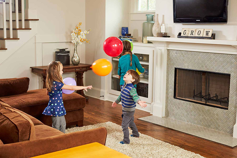 kids playing with balloons in living room