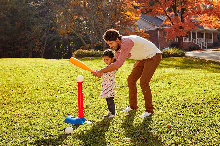 dad and daughter hitting ball off a tee