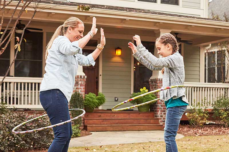 mom and daughter hula hooping outside