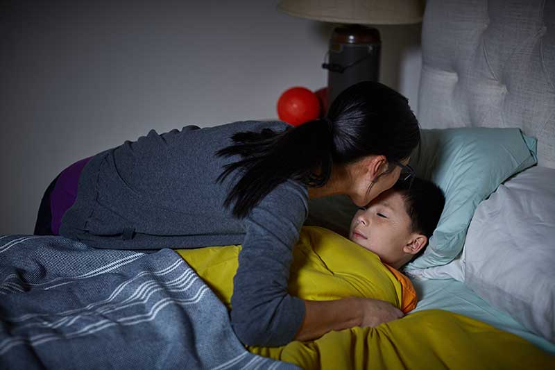 mom tucking son into bed