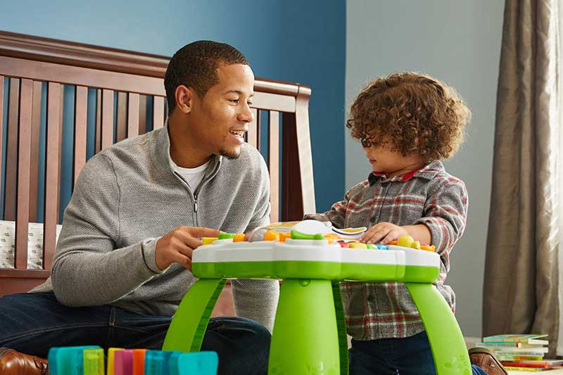 dad playing with toddler son in bedroom