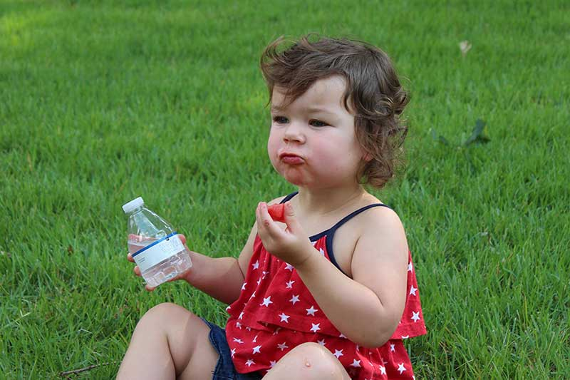 toddler with watermelon and bottled water