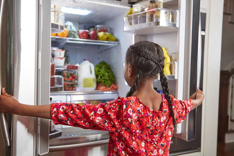 girl looking in fridge