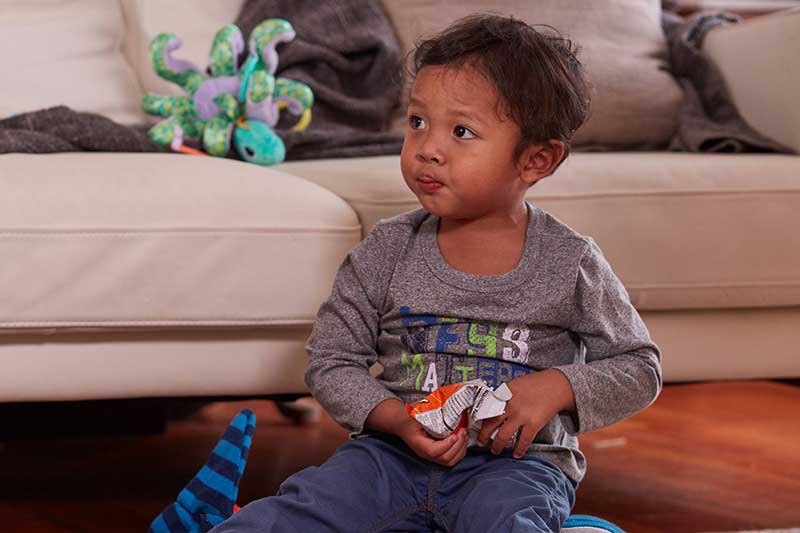 toddler snacking while playing