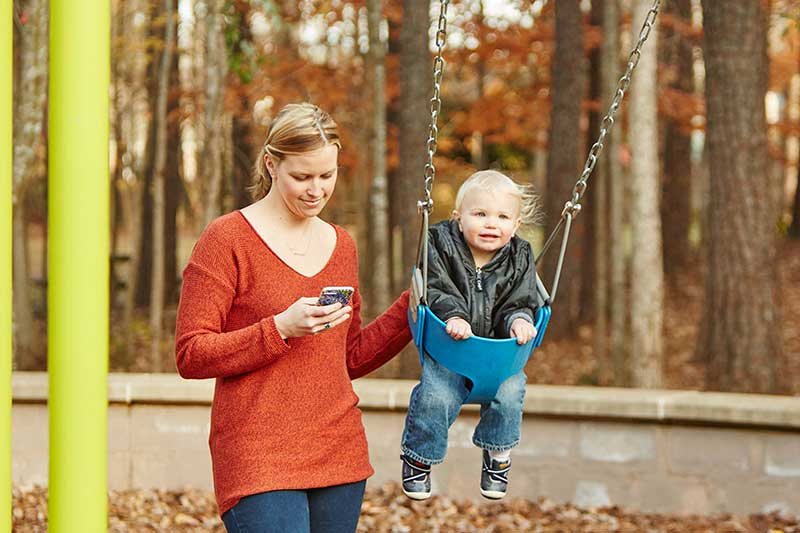 mom on phone with baby on swing