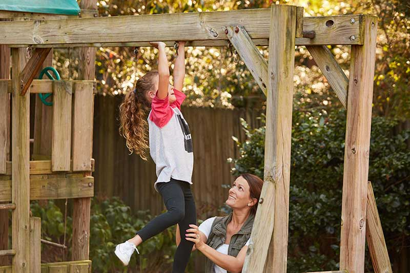 mom watching daughter on monkey bars